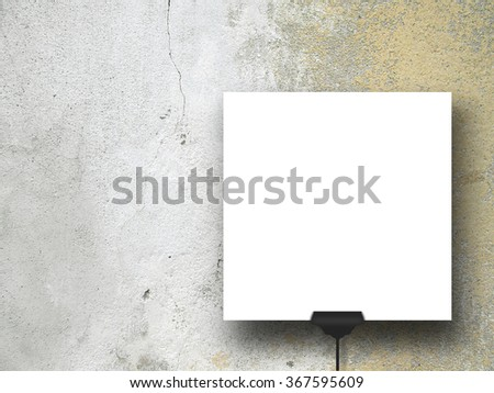 Close-up of one square paper sheet with clip on grey and brown weathered concrete wall background