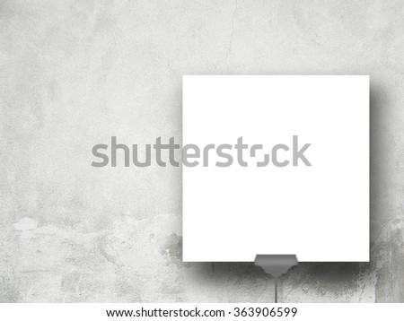 Close-up of one square paper sheet with clip on grey weathered concrete wall background