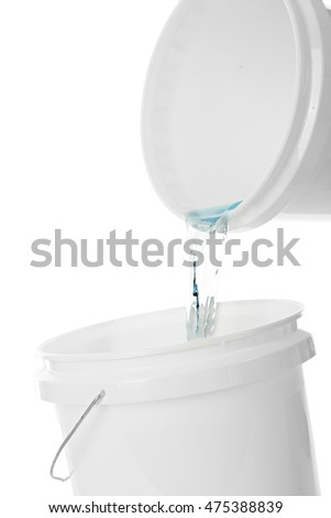 Close-up of one white plastic bucket pouring water into another white plastic bucket.  On a white background.