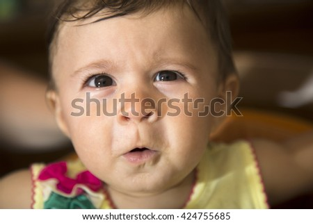 Close-up of one year old kid looking up with funny face