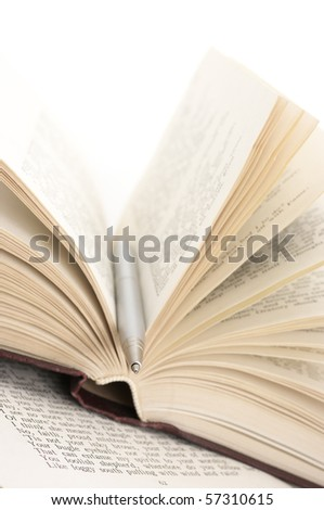 Close-up of open book and pen on white background.