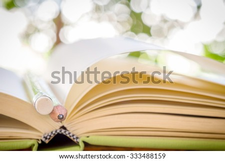 Close up of open book and pencil on bokeh background, shallow deep of field on pencil and soft focus process - stock photo