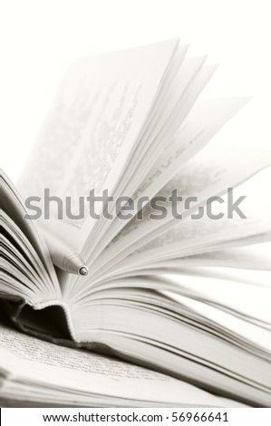Close-up of open books and pen on white background. Sepia. - stock photo