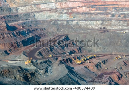close up of open cast mine extracting iron ore with heavy trucks, excavators, diggers and locomotives