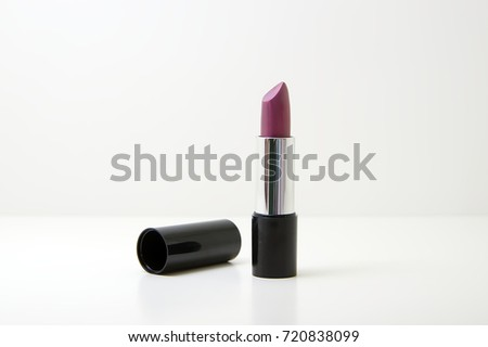 Close up of open lipstick purple color on a white background