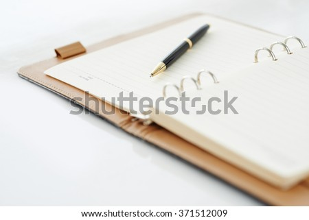 Close-up of open personal organizer with pen - stock photo
