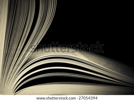 Close-up of opened book pages against black background. Space for text. Shallow DOF. - stock photo