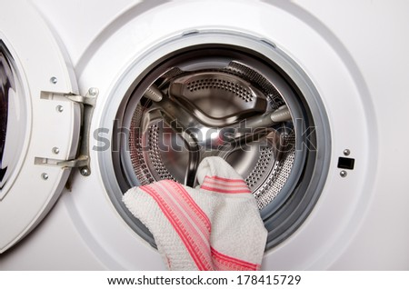 Close up of opened door of washing machine with towel in it - stock photo
