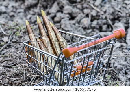 close up of orange chrome shopping cart with bullets on dirty clay - stock photo