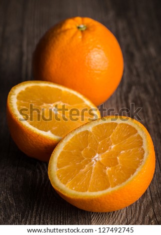 Close-up of orange fruit on old wooden board.  Focused on the middle of the front orange - stock photo