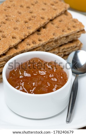 close-up of orange jam and crisp bread on a plate, vertical - stock photo