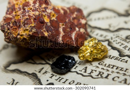 Close-up of ore deposits (gold, coal & bauxite) and an old map of Africa - stock photo