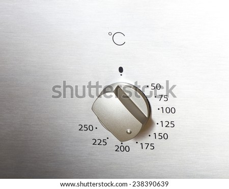 Close up of oven knob on metal board - stock photo