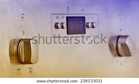 Close up of oven knobs and display on stainless steel board - stock photo