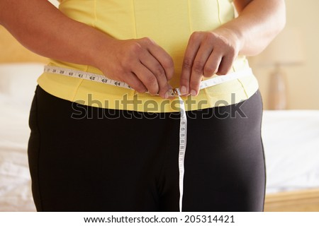 Close Up Of Overweight Woman Measuring Waist - stock photo