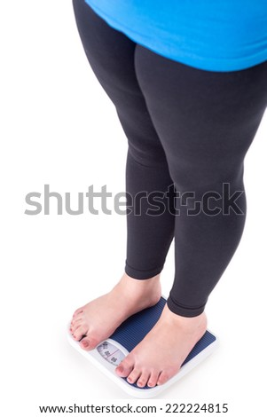 Close-up of overweight young woman standing on weighs, isolated on white - stock photo