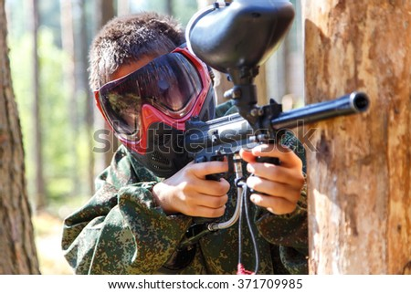 Close-up of paintball shooter in mask outdoors - stock photo