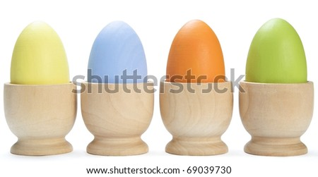 Close up of painted Easter craft eggs in cups lined up in a horizontal row.  White background with light shadows.