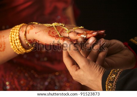 Close up of Pakistani couple's hands at a wedding, concept of marriage/partnership/commitment - stock photo