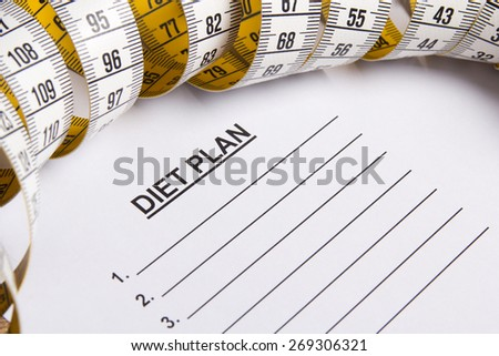 close up of paper with diet plan and yellow measure tape - stock photo