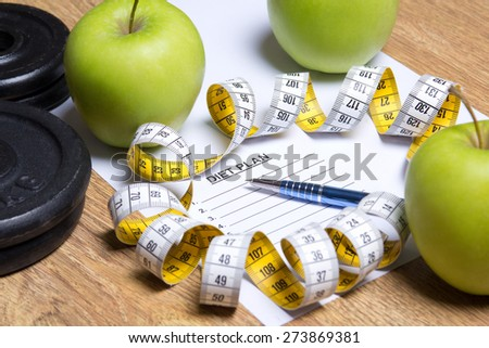 close up of paper with diet plan, apples, dumbbells and yellow measure tape - stock photo