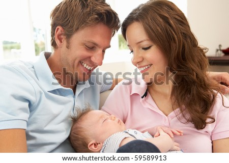 Close Up Of Parents Cuddling Newborn Baby Boy At Home