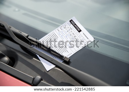 Close-up of parking ticket on car's windshield - stock photo