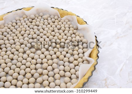 Close-up of pastry weights, ceramic beans, in an unbaked pie case lined with baking parchment - stock photo