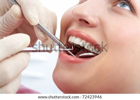 Close-up of patient?s open mouth during oral inspection with mirror and hook