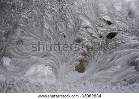 Close up of patterns formed by ice on glass surface. - stock photo
