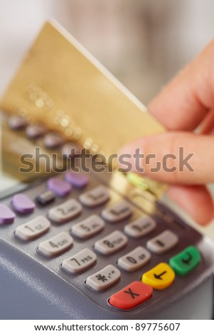 Close-up of payment machine buttons and human hand holding plastic card - stock photo
