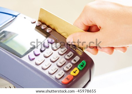 Close-up of payment machine while human hand keeping plastic card in it - stock photo