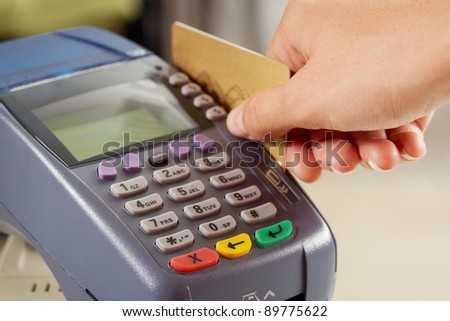 Close-up of payment machine while human hand keeping plastic card in it