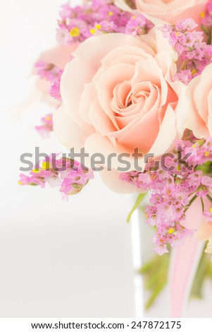 Close up of peach roses arrangement with statice in a glass vase and ribbon. - stock photo