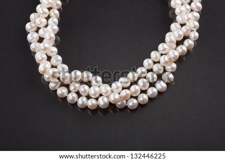 Close-up Of Pearl Bracelet Over Black Background - stock photo