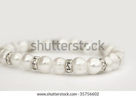 Close up of pearls and diamond jewel - stock photo