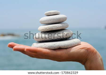 Close-up of pebble pile in woman's hands with sea background - stock photo