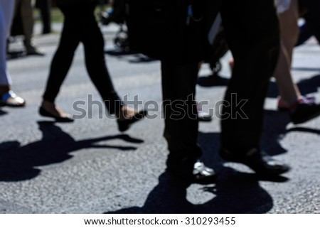 Close up of pedestrian crossing and people walking in hurry - stock photo