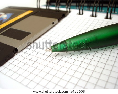 close-up of pen and diskette on notebook - stock photo