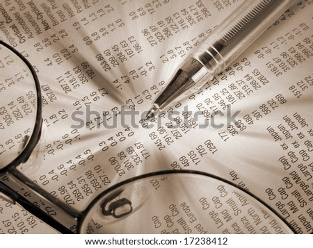 Close-up of pen and glasses on financial newspaper - stock photo