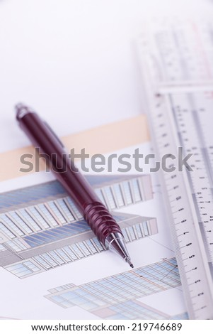 Close up of pen and ruler on blueprints of building - stock photo