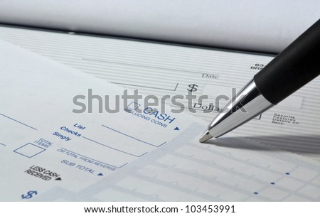 Close up of pen filling out a personal banking deposit slip with check in background and copy space.