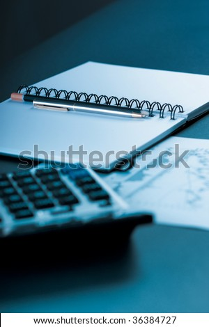 Close up of pen, pencil and worksheet with calculator and stock chart - stock photo