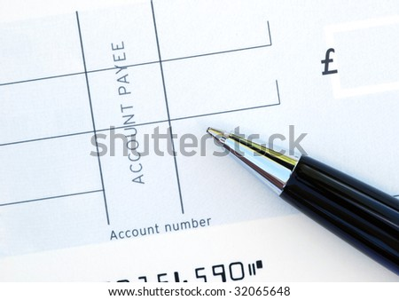 Close-up of pen resting on blank cheque