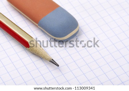 Close up of pencil and eraser on paper page - stock photo