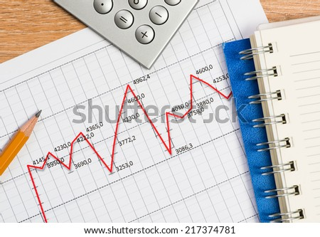 close-up of pencil, notebook and graph growth