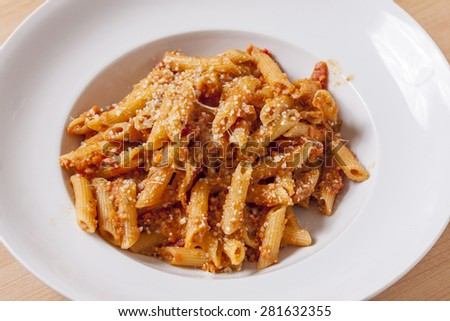 Close-up of penne pasta and tomato sauce in a white bowl topped with Parmesan cheese - stock photo