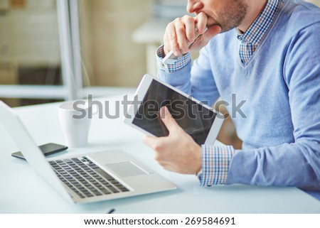 Close-up of pensive businessman working with touchpad and laptop in office - stock photo