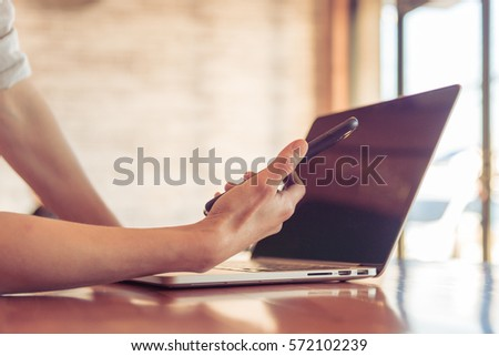 Close up of people hand using smartphone and laptop on wooden table in technology and business concept