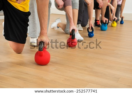 Close-up Of People Holding Colorful Kettle Bell Weights - stock photo